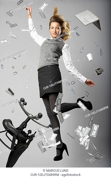 young business woman jumping with flying office objects