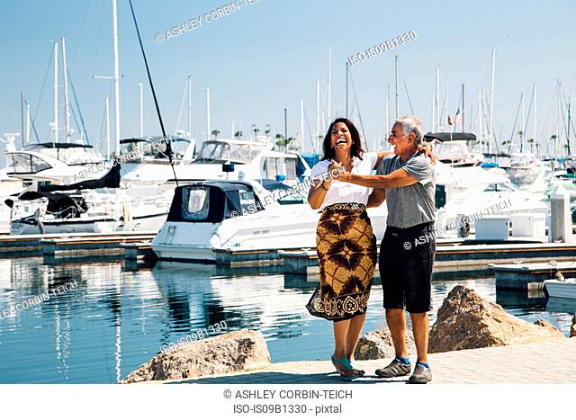 Senior couple dancing outdoors, beside harbour, Long Beach, California, USA