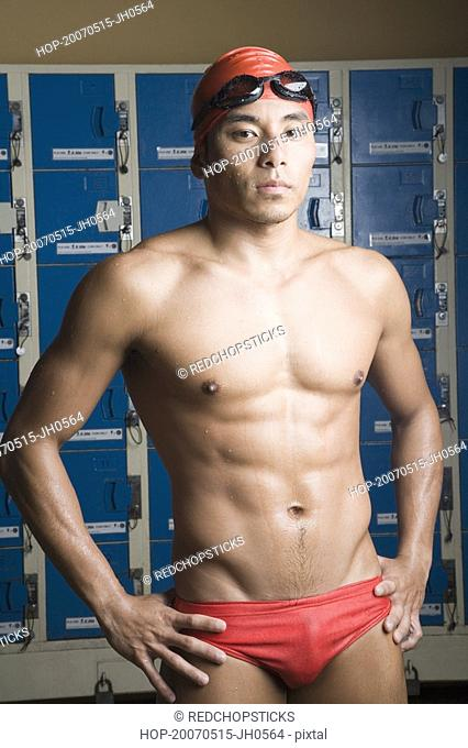 Portrait of a young man standing in a locker room