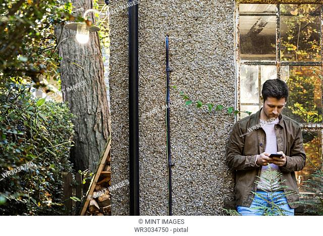 A young man using a smart phone standing in a courtyard