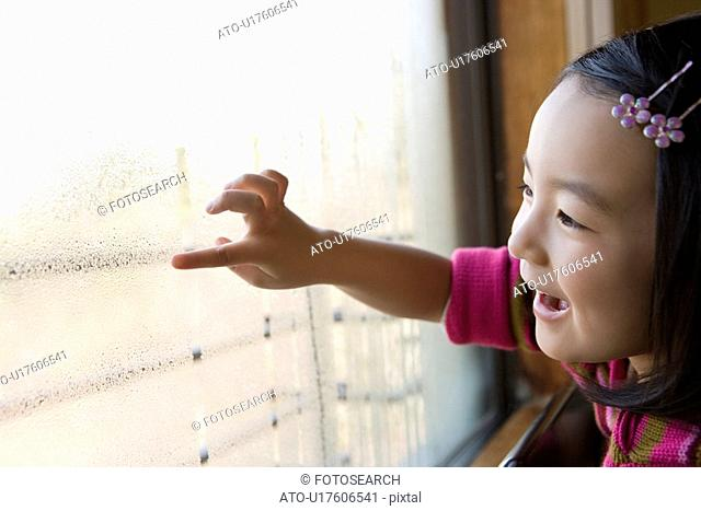 Girl drawing on window, smiling