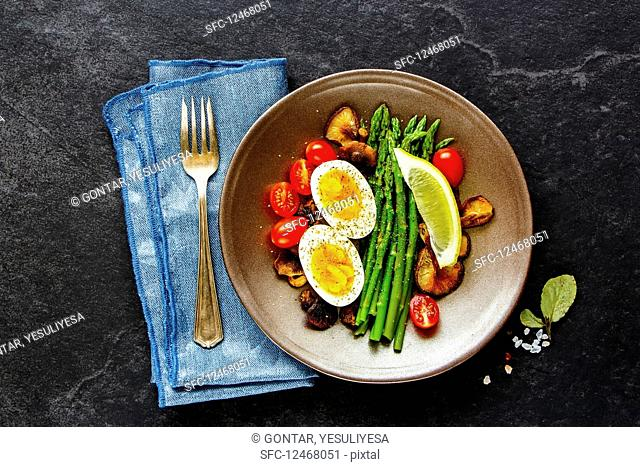 A healthYes vegetarian breakfast with eggs, asparagus, mushrooms and tomatoes