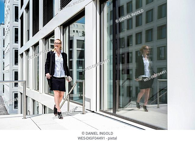 Smiling businesswoman with newspaper walking in front of office building