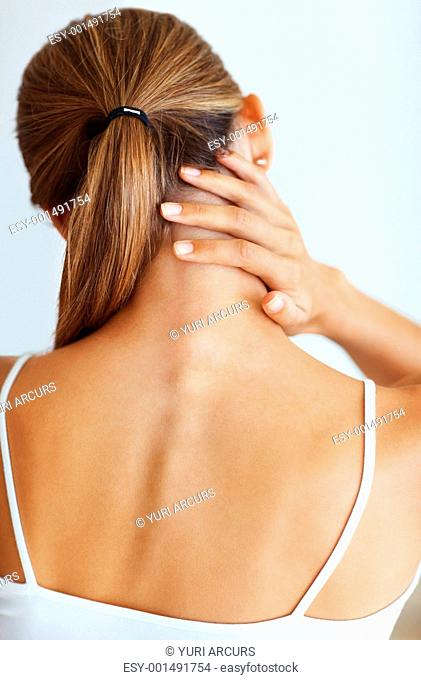 Rear view of young woman suffering from severe neck ache