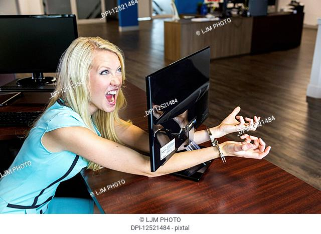 Young millennial business woman handcuffed to her computer monitor in the workplace; Sherwood Park, Alberta, Canada