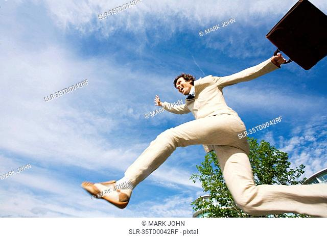 Businessman jumping for joy outdoors