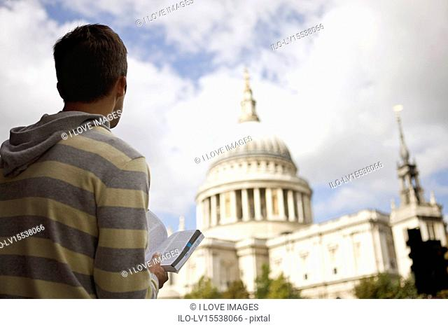 A mid-adult man standing in front of St Paul's cathedral, looking at a guidebook