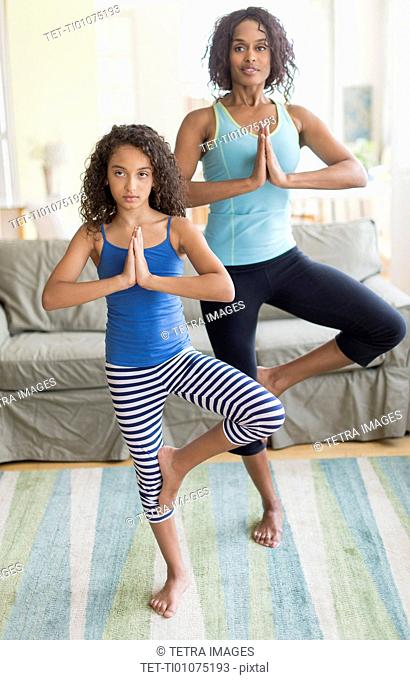 Mother and daughter (8-9) doing in yoga poses in living room