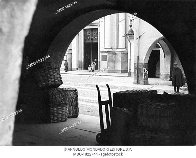 A man in cloak standing in front of some wicker baskets piled up under the arcades on via Roma. A woman coming out with a child from the church of Saint Ambrose
