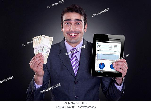 Portrait of businessman with currency and digital tablet