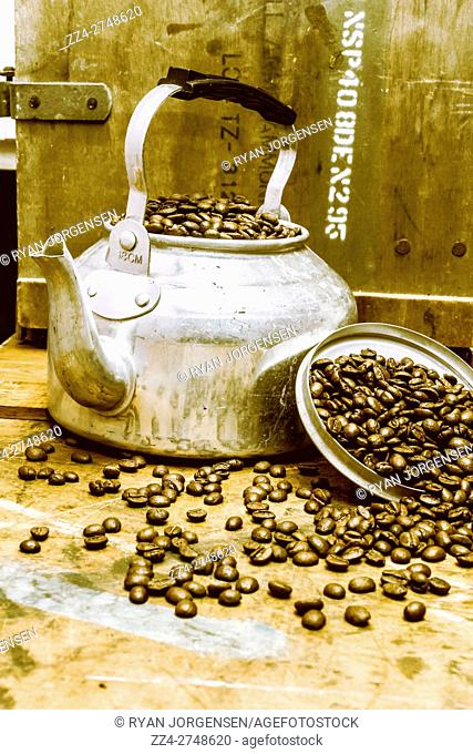 Antique wooden kitchen decoration of a vintage kettle in a spill of exotic coffee beans. Bakehouse art