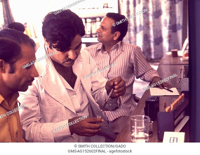 Photograph of three laboratory workers, one testing a blood sample as part of a malathion poisoning study, Pakistan, 1977