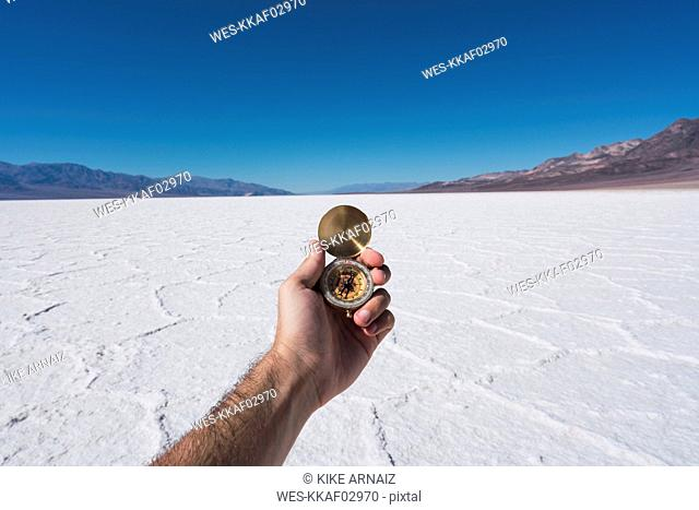 USA, California, Death Valley, man's hand holding compass