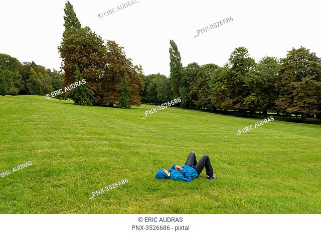 Teen boy lying on the grass alone in a beautiful park
