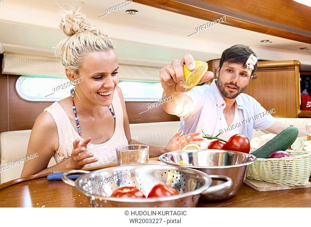 Young couple eating in cabin of yacht, Adriatic Sea