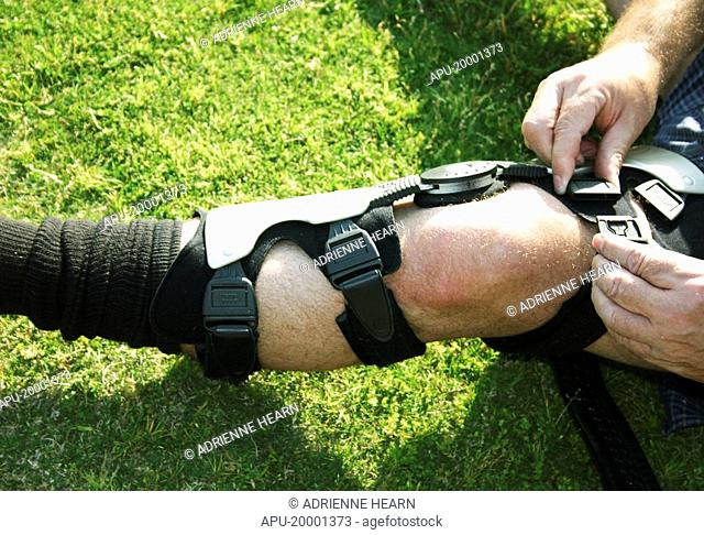 Football player adjust knee brace before playing game
