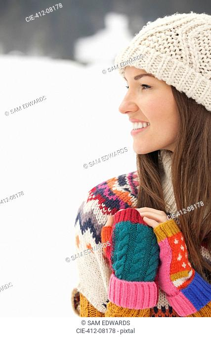 Close up of smiling woman wearing knit hat and fingerless gloves in snowy field