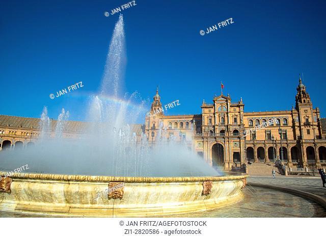 fountain with rainbow at plaza de espana, sevilla, spain