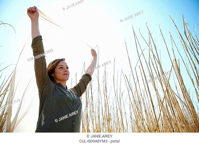Young woman holding up scarf in reeds