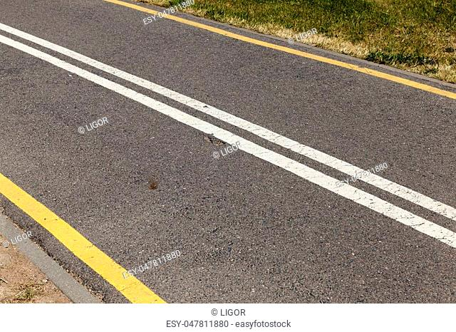 white and yellow lines on an asphalt narrow road, close-up photo