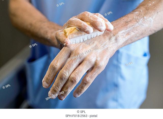 Doctor scrubbing hands with brush in hospital