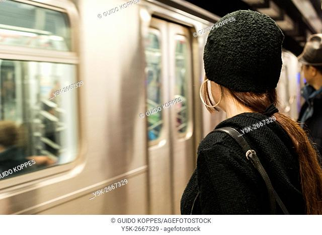 New York City, USA. Female commuter in the Manhattan subway observing her connecting train to arrive at the platform