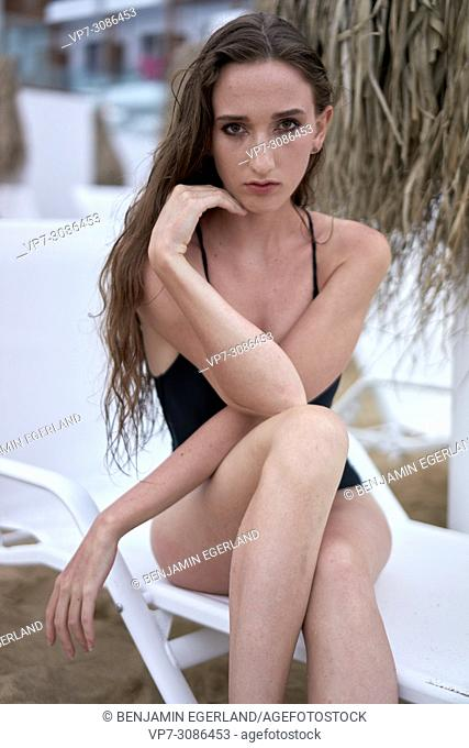 Greece, Crete, Malia, model woman sitting on sunbeds