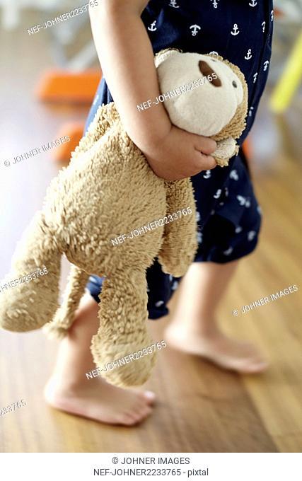 Child holding stuffed toy