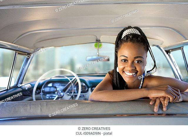 Woman turning around from front seat of vintage car