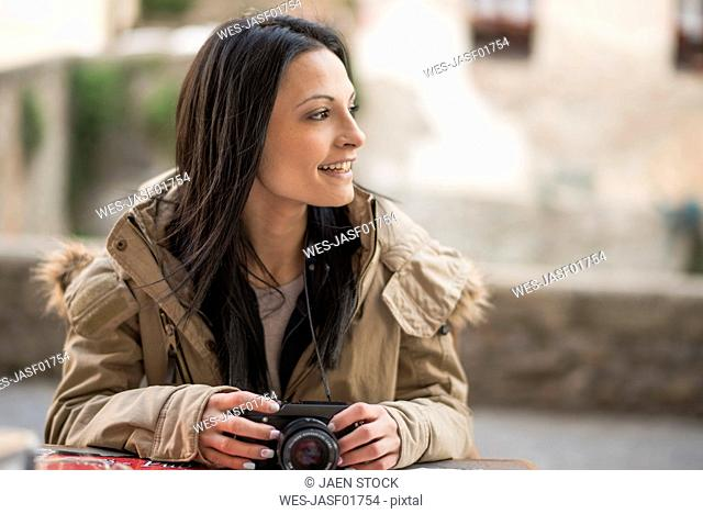 Smiling young woman with camera outdoors
