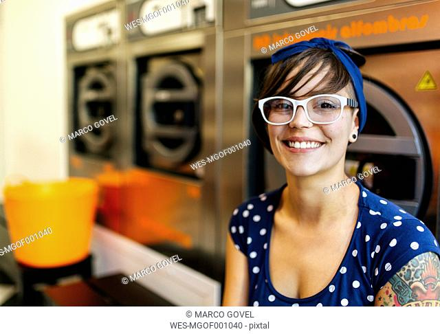 Portrait of smiling young womanwearing glasses in a launderette