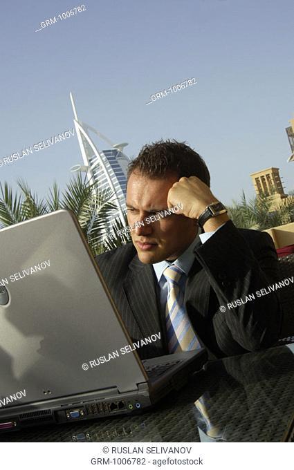Thinking businessman working on laptop in Dubai (Burj Al Arab hotel in background)