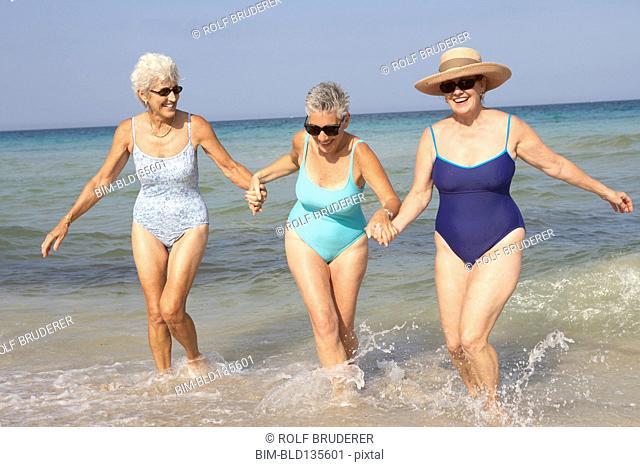 Senior women walking in waves on beach