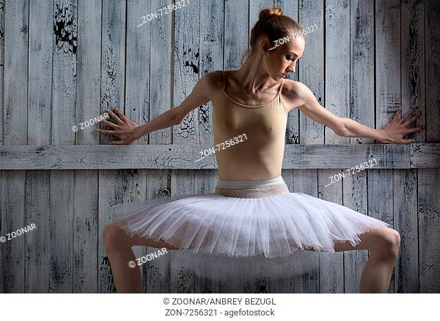 Ballerina standing near a wooden wall on pointe