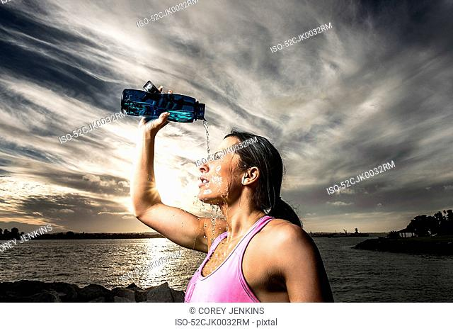 Runner pouring water on herself