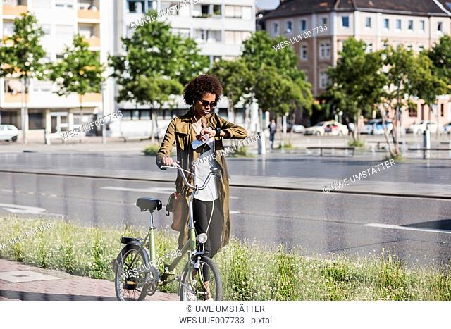 Young woman with with bicycle checking the time