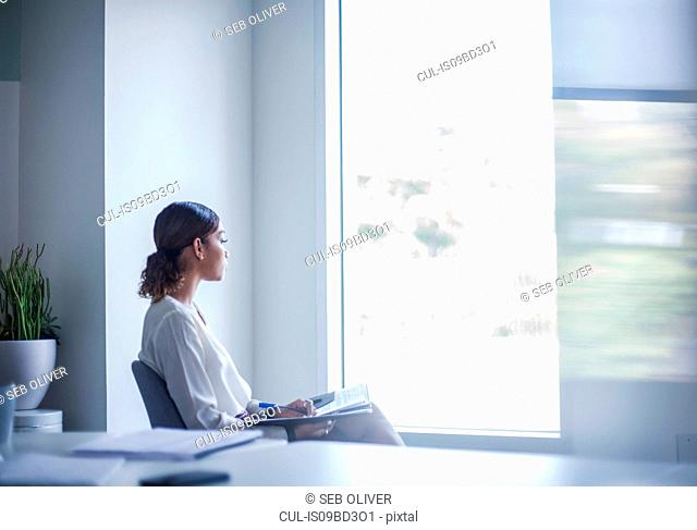 Businesswoman sitting in office looking out of window