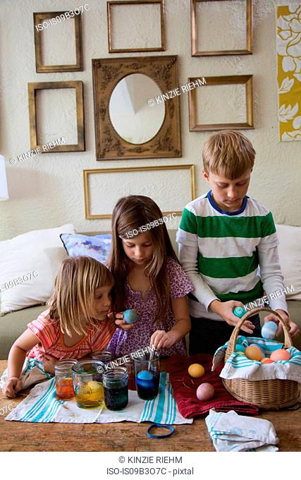 Boy and two sisters dyeing easter eggs in jars at table