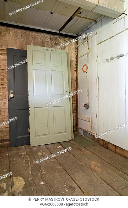 Stacked wooden doors and partially demolished plaster and wooden wall in a empty room inside an old 1800s cottage style home, Quebec, Canada
