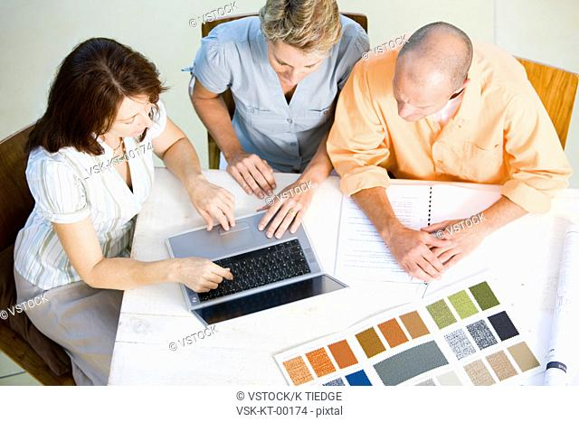Couple and interior designer choosing color sample from laptop, high angle view