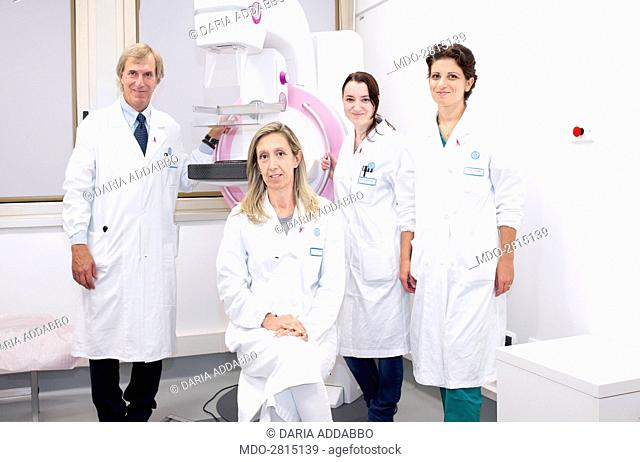 A medical team posing at the hospital beside a mammograph. Rome (italy). 16th September 2014