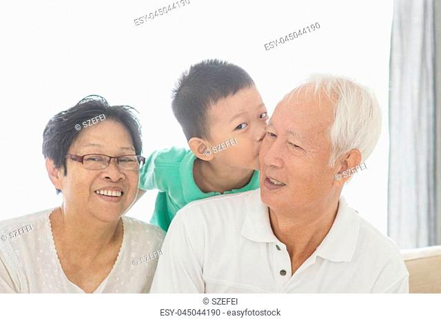 Portrait of happy Asian grandchild kissing grandparents at home, old senior retired people and child indoor lifestyle