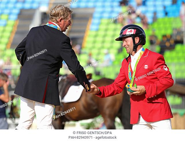 Gold medalist Nick Skelton of Great Britain (Big Star) and Bronze medalist Eric Lamaze of Canada (FINE LADY 5) celebrate on the podium during the medal ceremony...