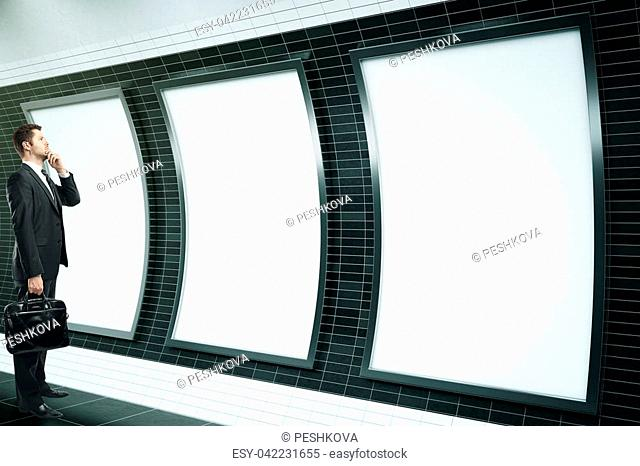 Thoughtful businessman looking at three empty ad posters in metro station with dark tile walls. Side view, Mock up, 3D Rendering