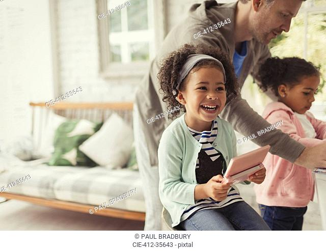 Laughing girl using digital tablet in living room