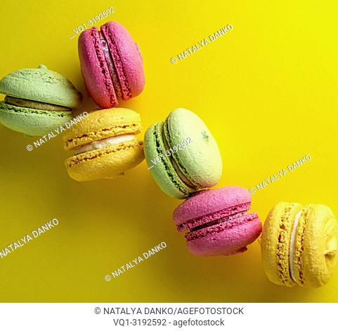 multicolored round macarons almond flour cakes on a yellow background
