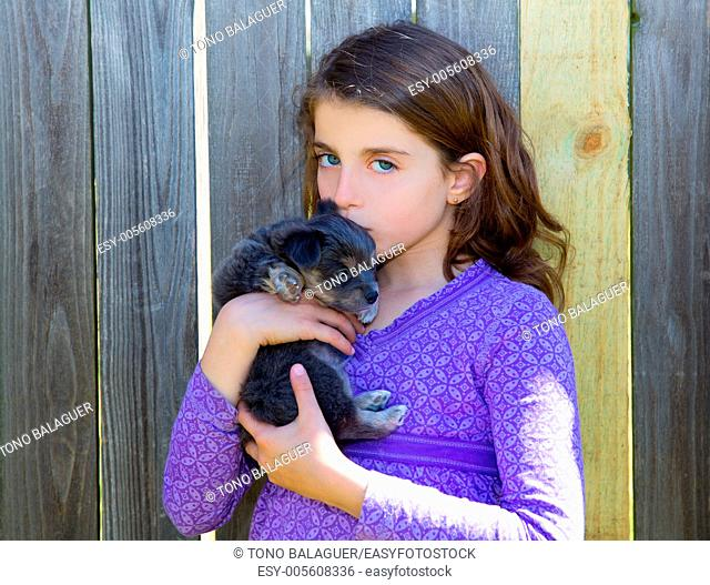 children girl kissing her puppy chihuahua doggy on the wood fence