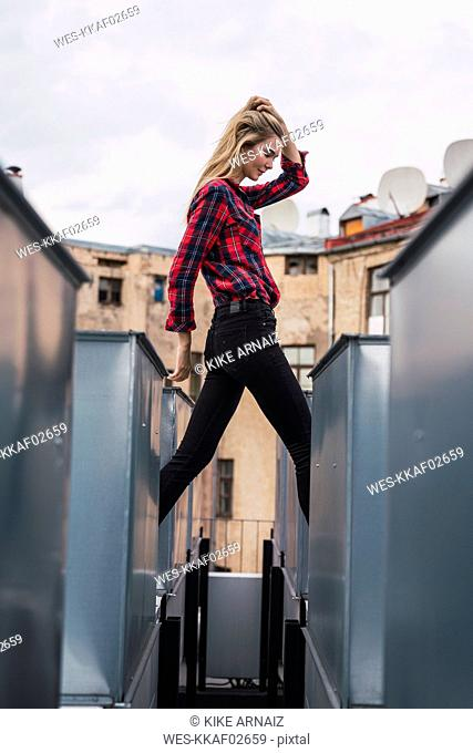 Fashionable young woman on rooftop wearing plaid shirt and black jeans