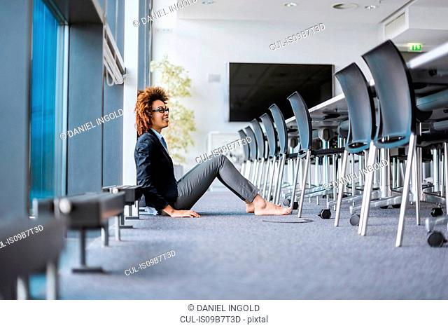 Happy barefoot young businesswoman sitting on boardroom floor