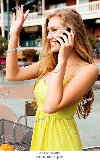 Woman on mobile phone waving
